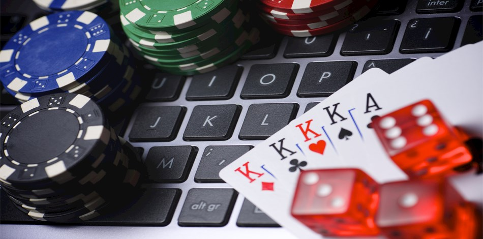 Gambling chips, dice and playing cards on a keyboard